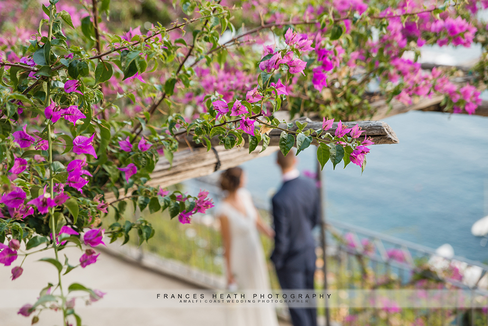 Wedding portrait of bride and groom with bougainvillea