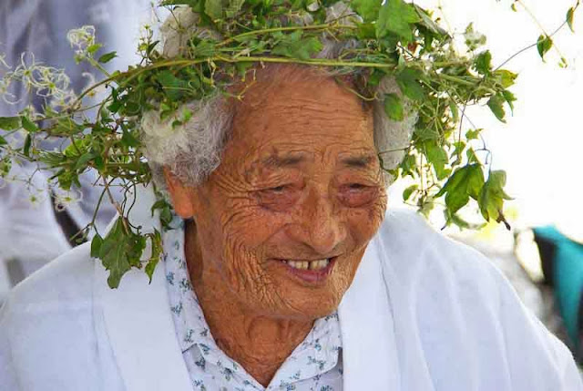 elderly woman wearing wreath and white robes, priestess