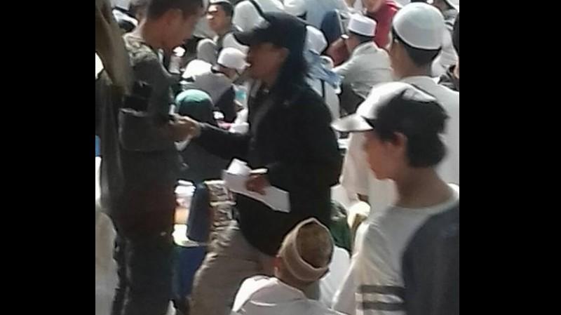 Seorang pria bagi-bagi amplop dalam aksi kawal Rizieq di Polda Metro