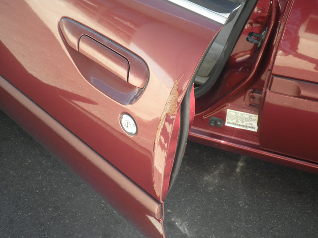 Dented door on 2000 Nissan Altima before repairs at Almost Everything Auto Body