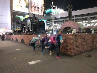 新橋駅前にあるSL機関車横で連結のポーズをとる4人