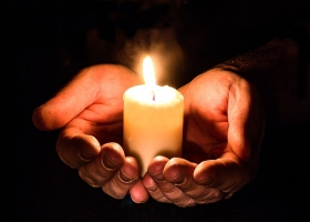 A picture of hands holding a candle.