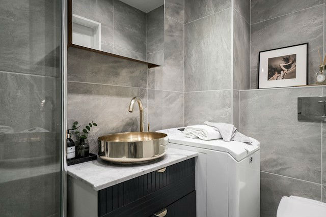 Balo con lavabo de superficie en color dorado y lavadora de carga superior