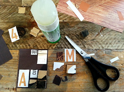 A selection of pieces of paper, scissors and a glue stick arranged on a table top.