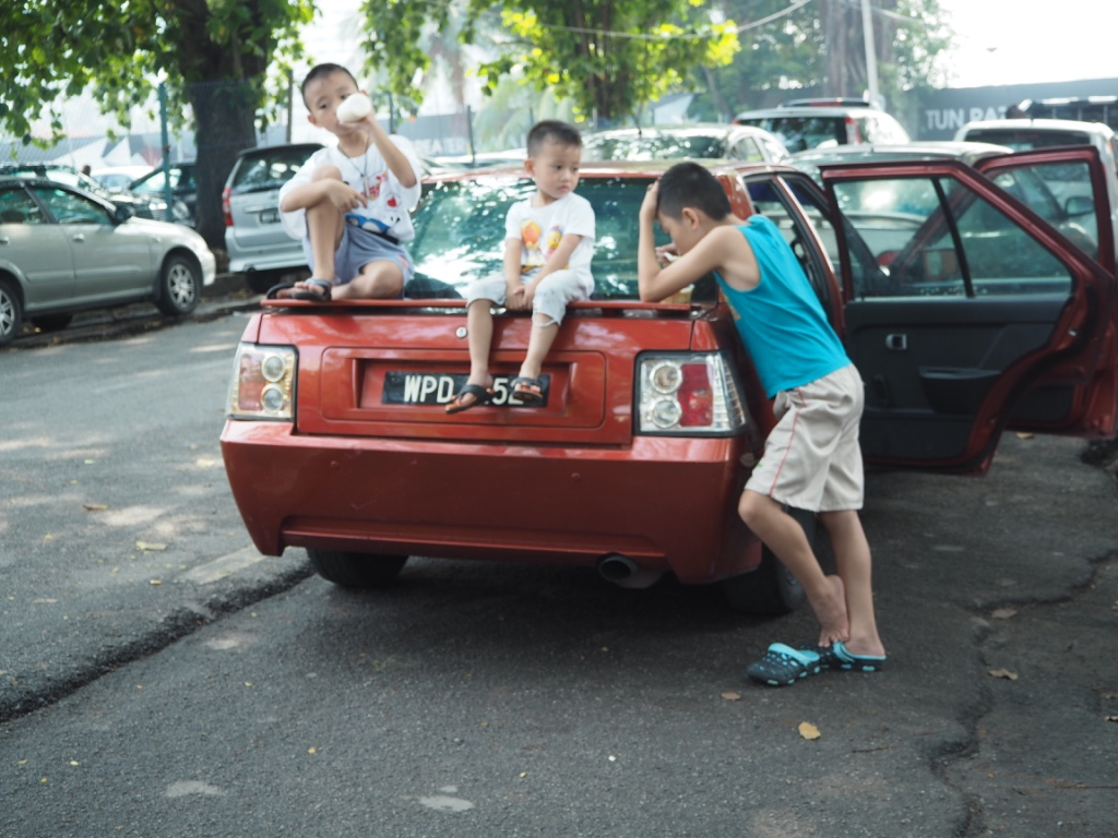 three little boys sat on car