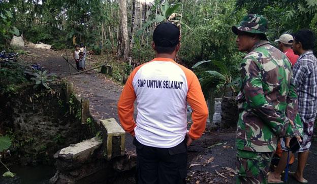 Petugas dan warga melihat kondisi jembatan