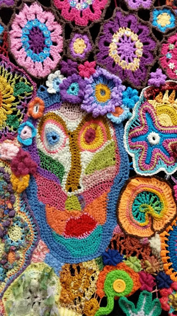 A close-up view of the multicoloured face on the first panel. Alongside are flowers, a 5-armed starfish shape and circular shapes.