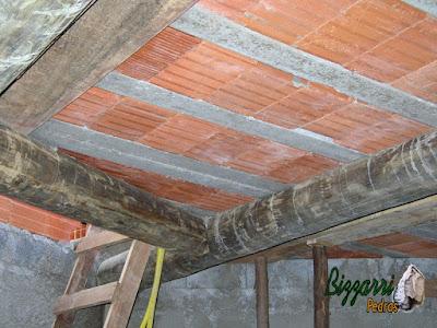 Detalhe da laje em cima da viga de madeira com os pilares de madeira e a alvenaria de bloco de cimento em construção rústica.