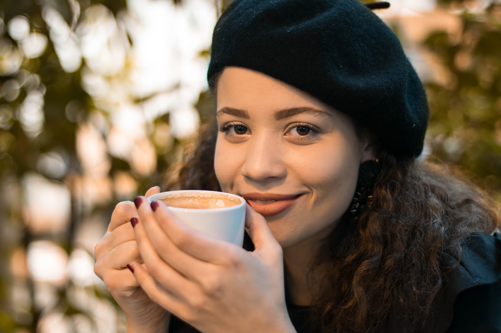 eboni holding a warm latte with Monica Vinader bracelet