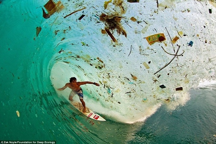 20 Pictures That Prove That Humanity Is In Danger - The Indonesian surfer Dede Surinaya rides a wave of filth and trash (Java, Indonesia)