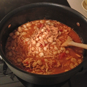 Adding hominy to the pot with chicken posole and red (rojo) sauce