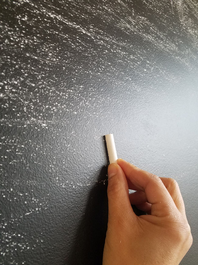 rubbing a piece of chalk on its side on chalkboard