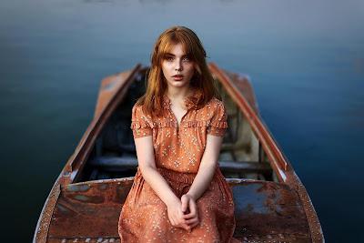Chica pelirroja sentada en un barco pequeño mirando a cámara desde un lago