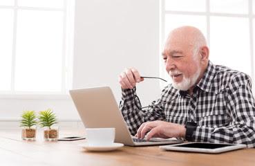 Persona mayor mirando un ordenador