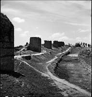 The Land Walls southwest of Tekfur Sarayı, May 1937. The Land Walls visually marking out the city. The movement of people along and through them, with the backdrop of the monuments of towers that disappear on the horizon, are typical of Artamonoff's photos [Credit: © Nicholas V. Artamonoff Collection, Image Collections and Fieldwork Archives, Dumbarton Oaks]