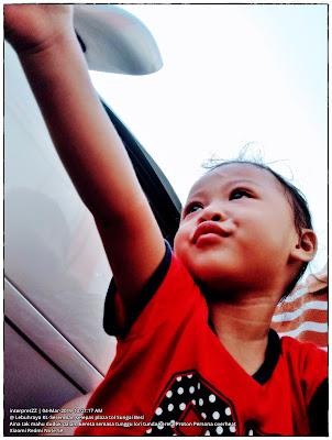 Gambar kanak-kanak perempuan berumur dua tahun sedang menunjuk ke arah kenderaan di lebuhraya terutamanya lori.