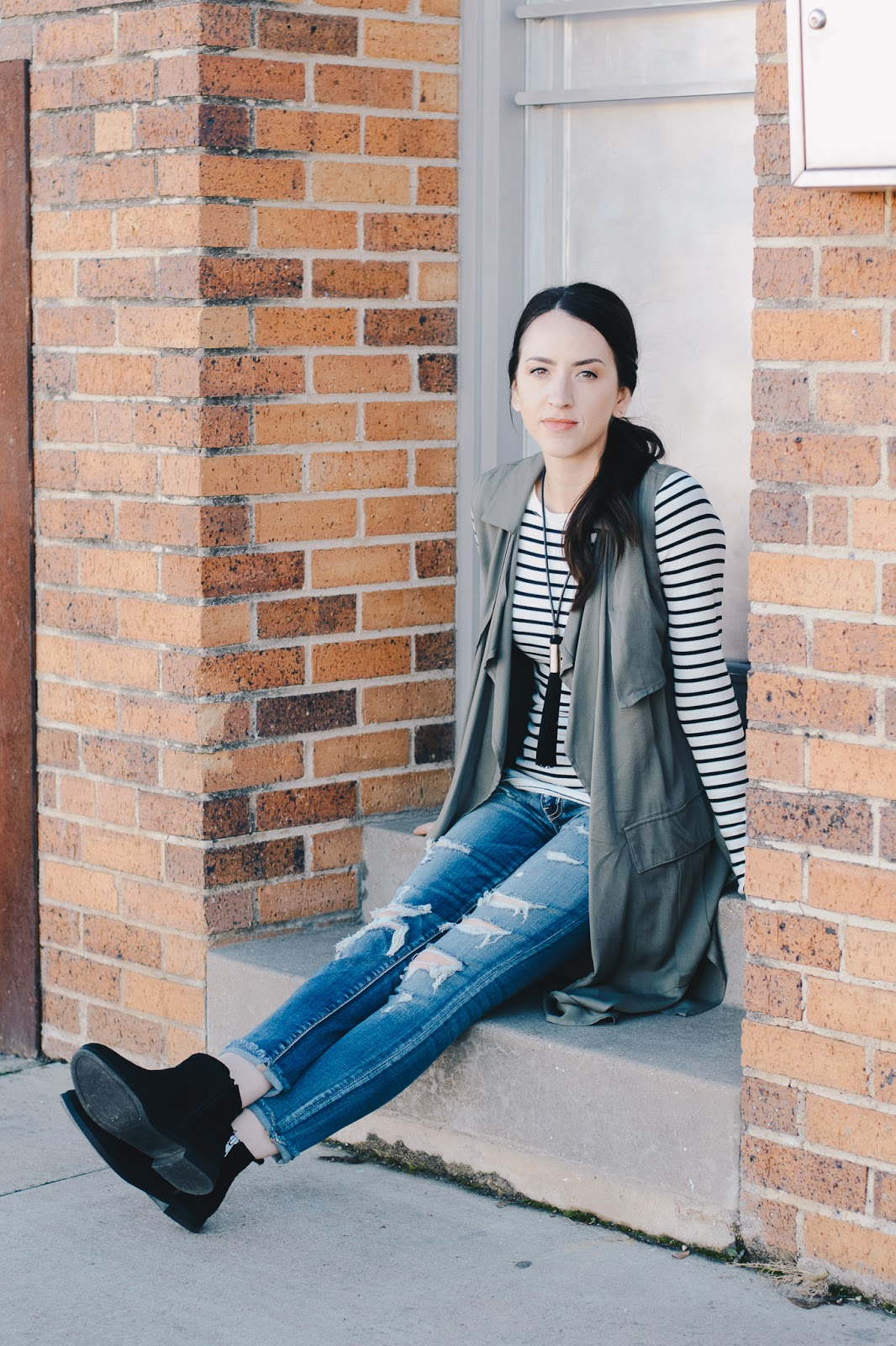 Distressed Denim and striped tee paired with long olive vest