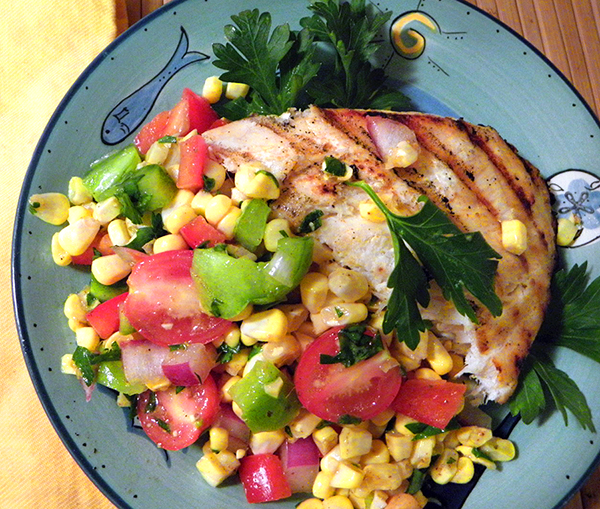 Closeup of Halibut and Corn Tomato Salad on Overflowing Plate
