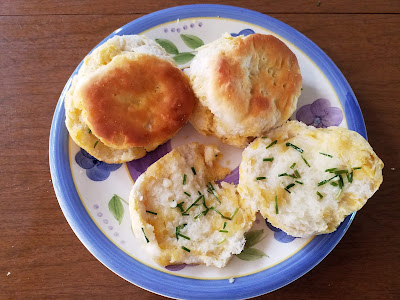 a purple flowered plate with three biscuits.  One is split in half to reveal it's been spread with chopped field garlic and butter.