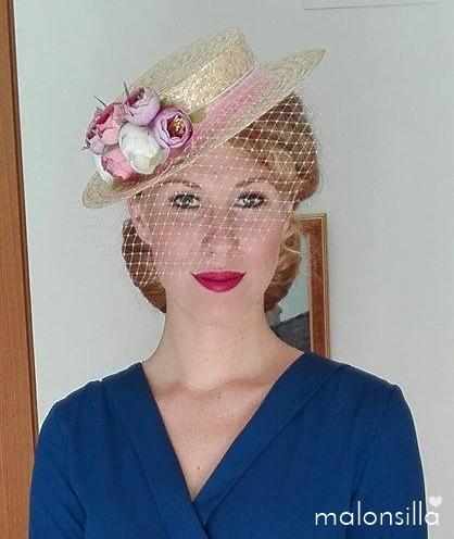 Invitada a boda con vestido azul azafata y sombrero paja con velo y flores en rosa y malva