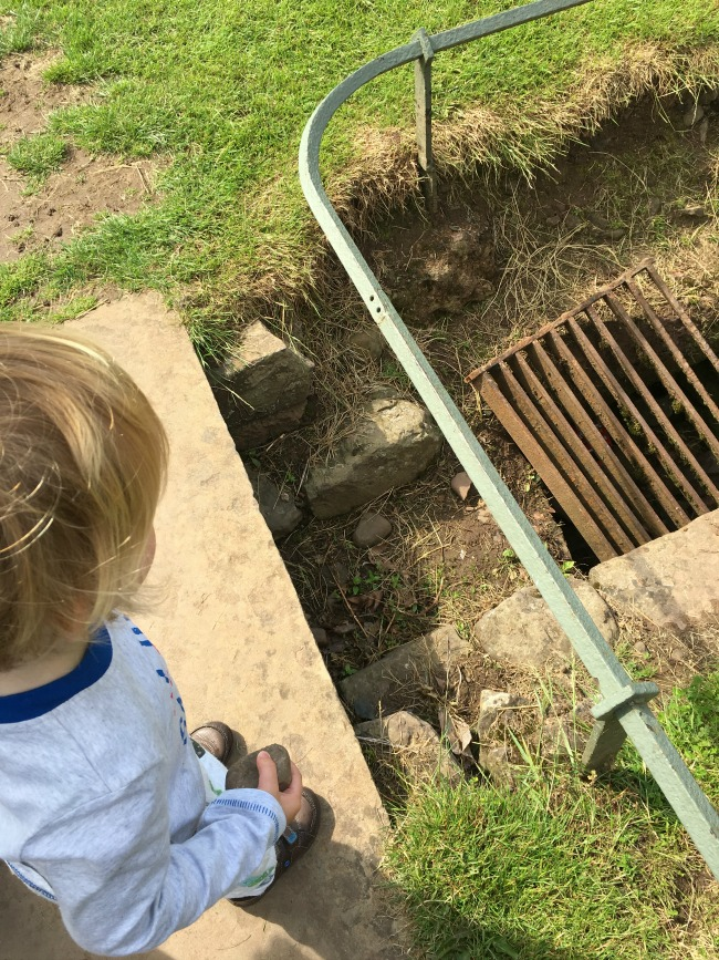 Caerleon-the-roman-fortress-of-isca-a-toddler-looking-at-drain