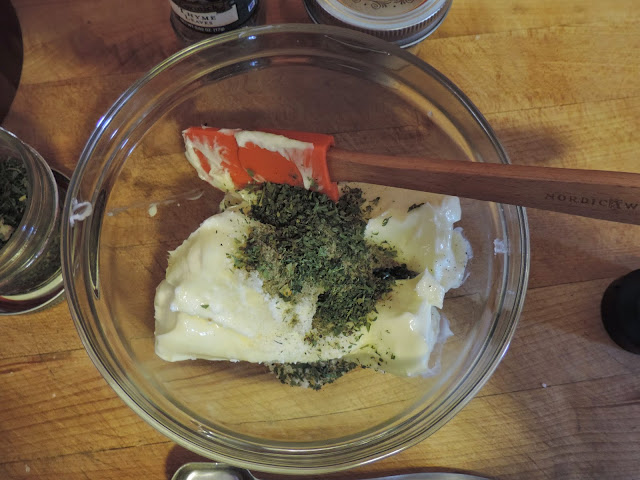 Dried herbs being added to the soften butter.
