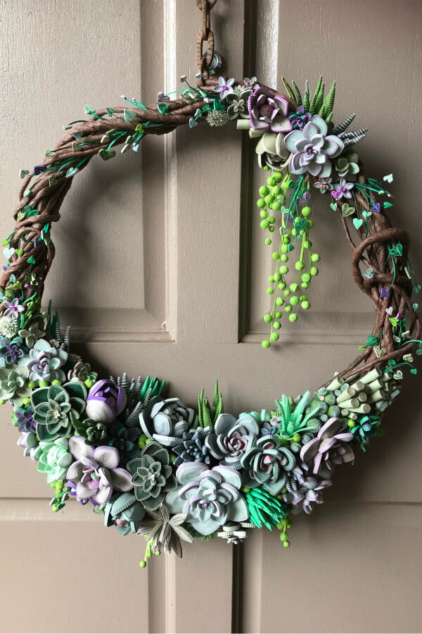 quilled succulent wreath hanging on door