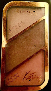 A rectangular palette filled with a light brown contour in one small rectangle, a darker brown in another rectangle and a bright highlight in another in a clear lid with kate moss written in pink cursive font with rimmel in bold font above it in the same size on a bright background.