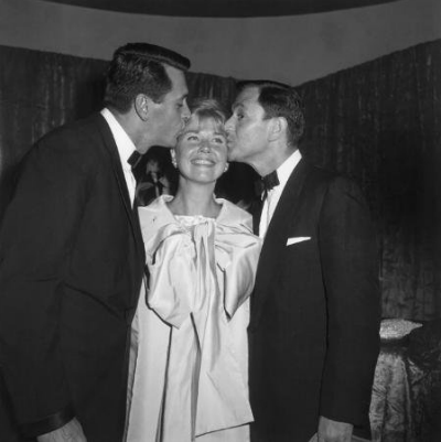 Rock Hudson and Tony Randall kissing Doris Day on the cheek at the premiere of Pillow Talk