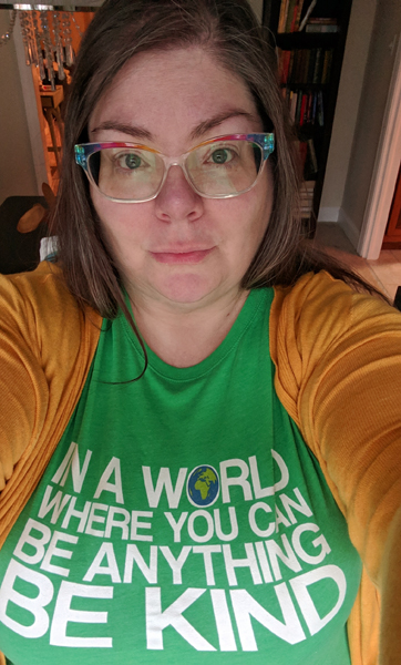 image of me wearing a green t-shirt that reads 'In a world where you can be anything, BE KIND'