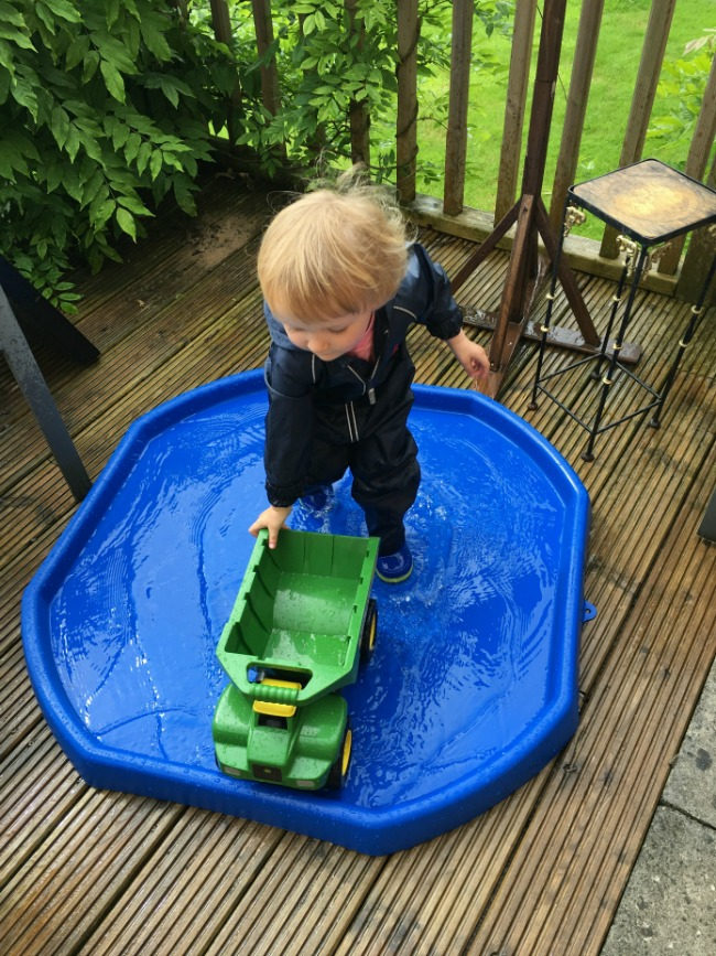 toddler-pushing-toy-lorry-in-water-on-tuff-spot