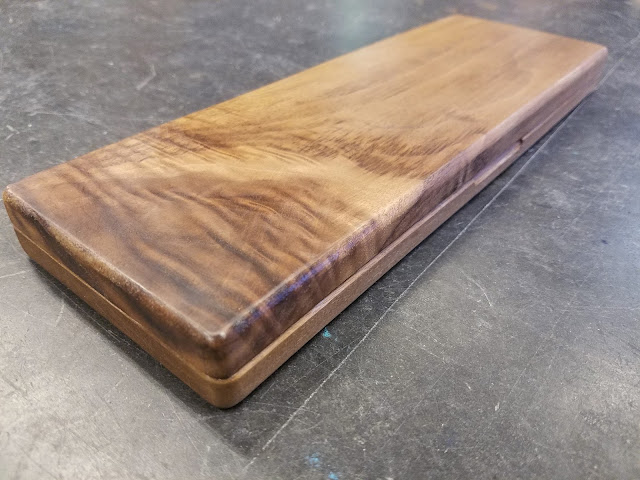 "walnut hinged box with dark striations and ""angel-step figure"" on the left side"