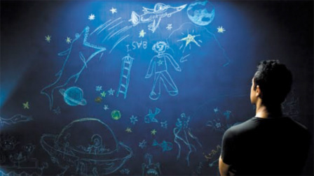 Ram Shankar Nikumbh, played by Aamir Khan, looks at some of Ishaan's artwork in Like Stars on Earth