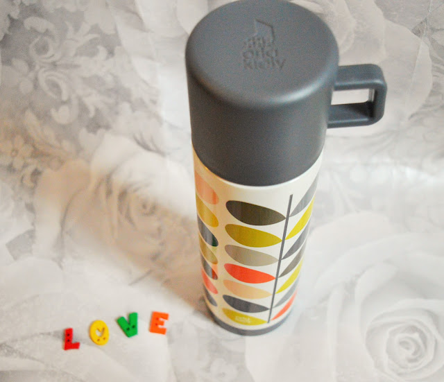 A funky and retro flask with green, grey and orange leaves.