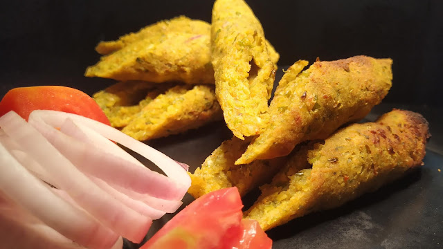 Garnished vegetable Seekh Kebab pieces with onions and tomatoes food recipe