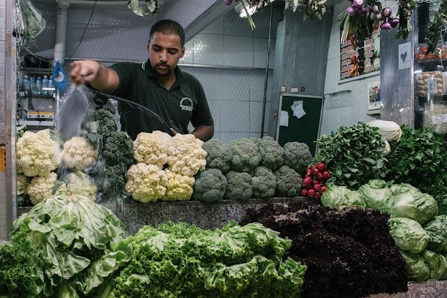 comerciante por trás da banca irrigando os vegetais expostos no mercado central