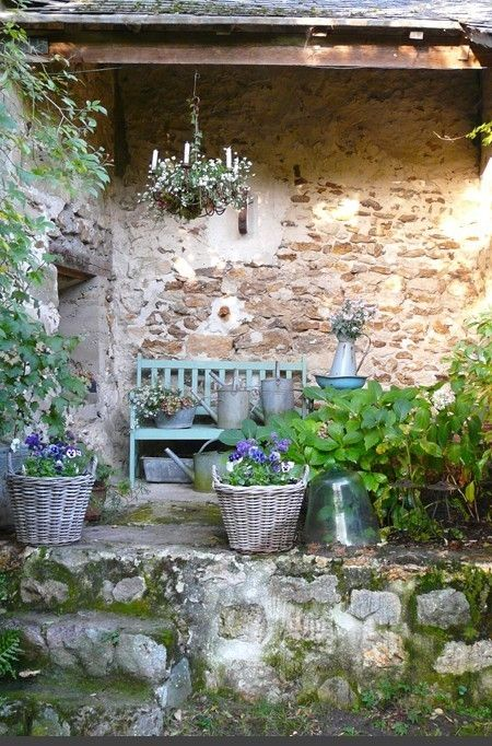 Charming #Frenchfarmhouse outdoor sitting area with rustic stone, chandelier, and green bench