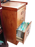 Photo of a wooden file cabinet with an open drawer and visible file folders