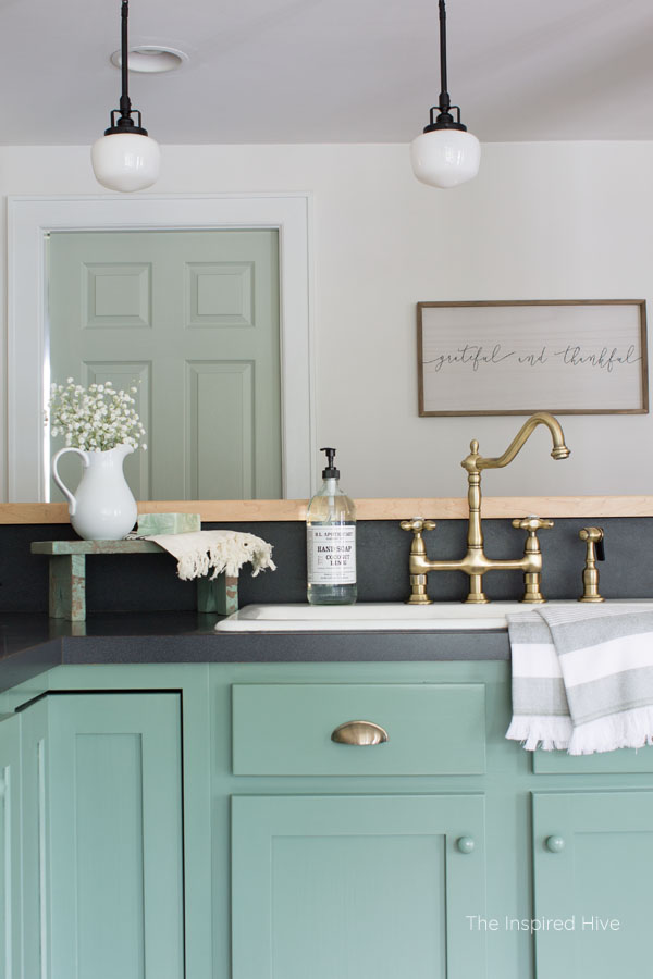 Vintage brass Heritage faucet. A cozy modern farmhouse kitchen with 1920s vintage charm. Exposed ceiling, schoolhouse lights, brass hardware, and porcelain knobs give this kitchen antique style.