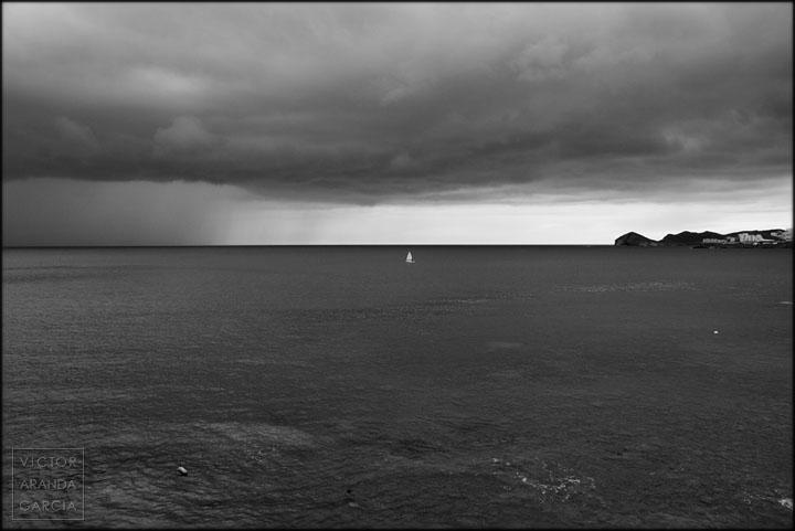 Un barco navegando entre la costa y la tormenta