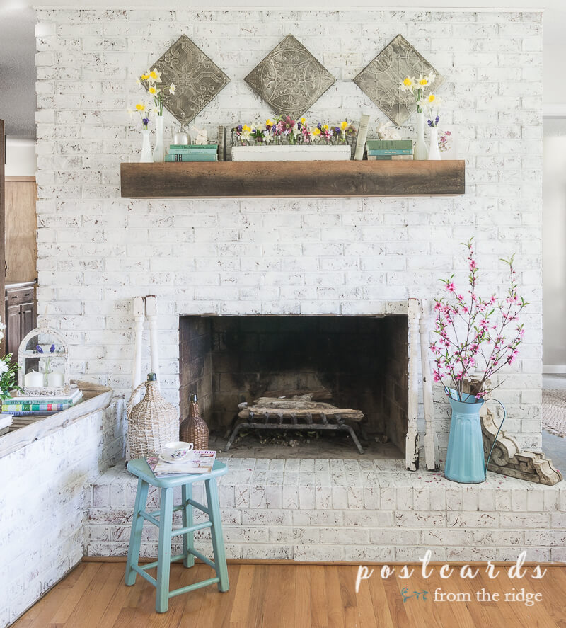 white painted brick fireplace with spring decor