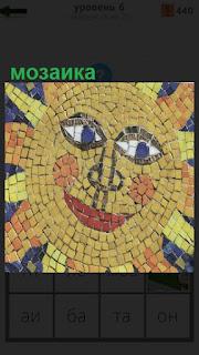 Крупным планом солнце сделанное из мозаики желтого цвета в виде лица