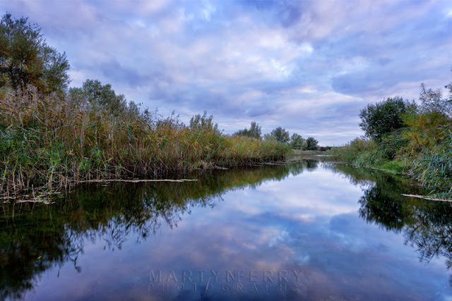 Clouds reflect in the River Ouse at the RSPB nature reserve in the Cambridgeshire Fens