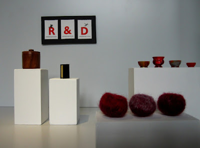 Modern miniature gallery space with plinths displaying two books, three felted bowls and four turned acrylic vases on plinths, and a letterpress triptych on the wall.