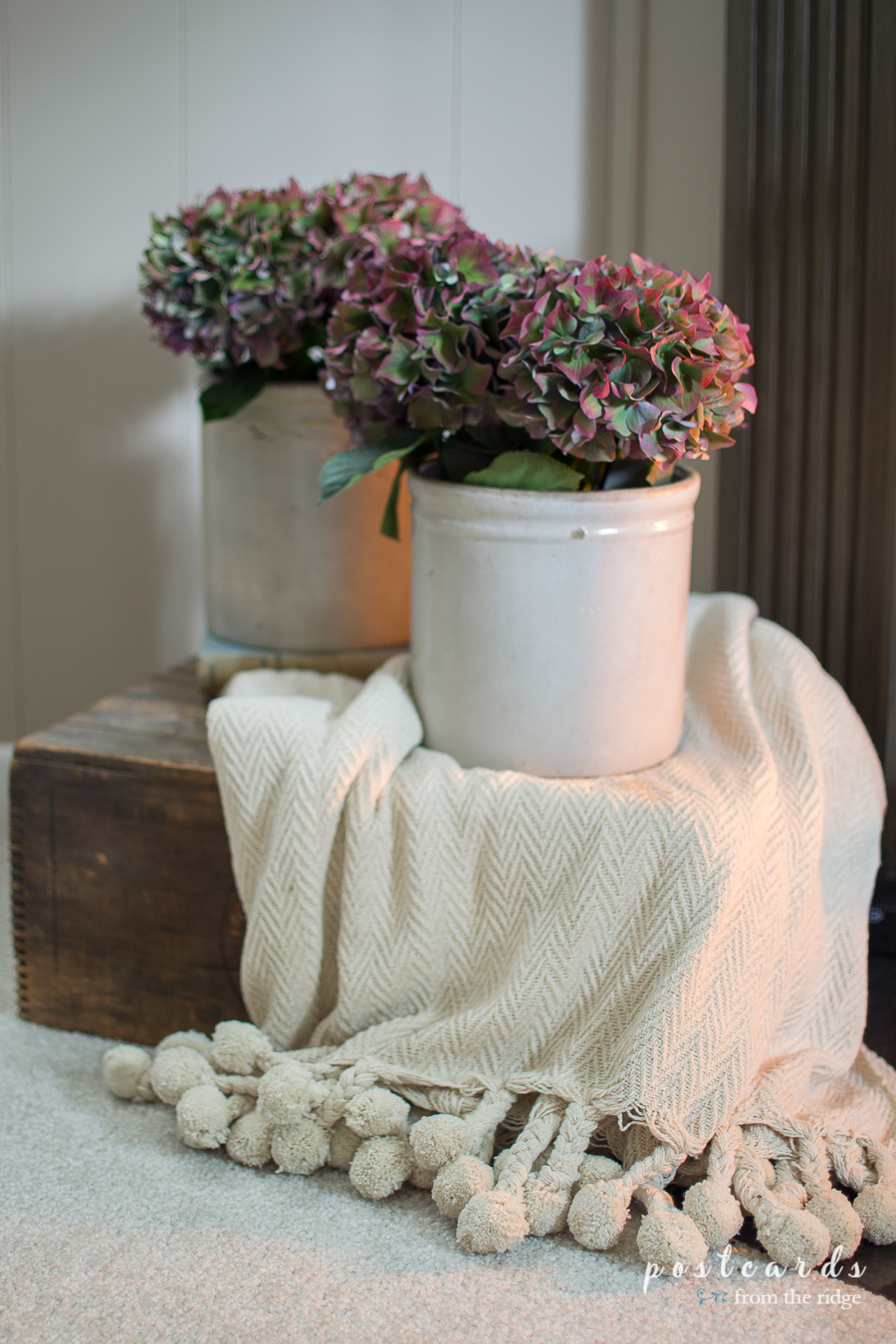 cozy throw blanket with pom poms and hydrangeas