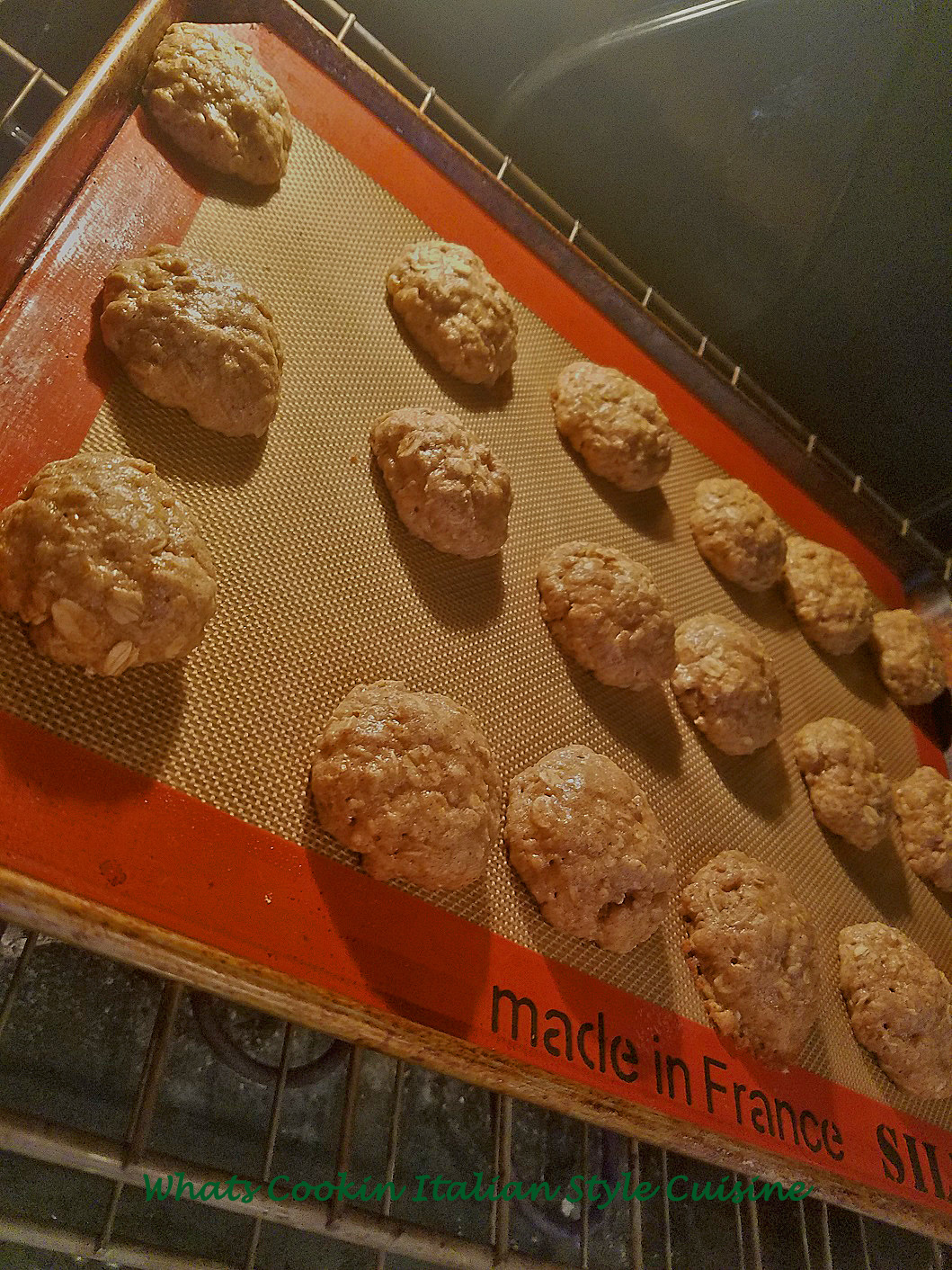 Old fashioned oatmeal cookies baked and cooling on a silpat mat cookie sheet