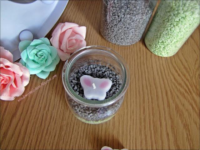 Kamyczki dekoracyjne i świeczka w szklanym naczyniu