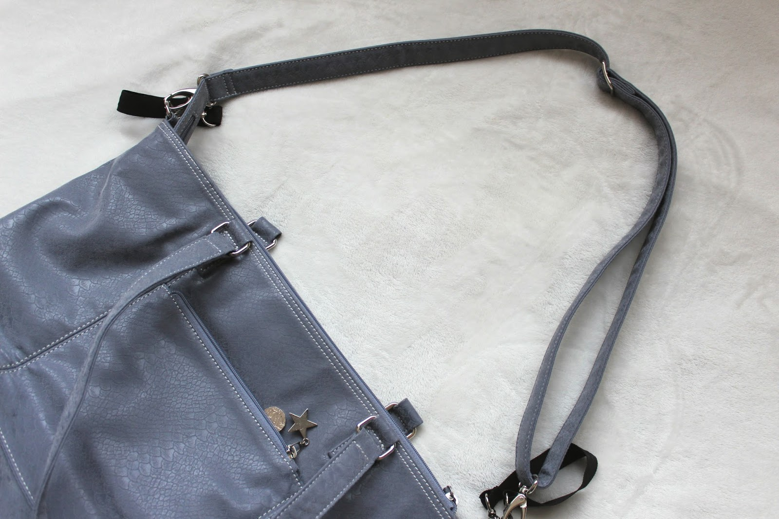 Large grey handbag with a long grey strap.