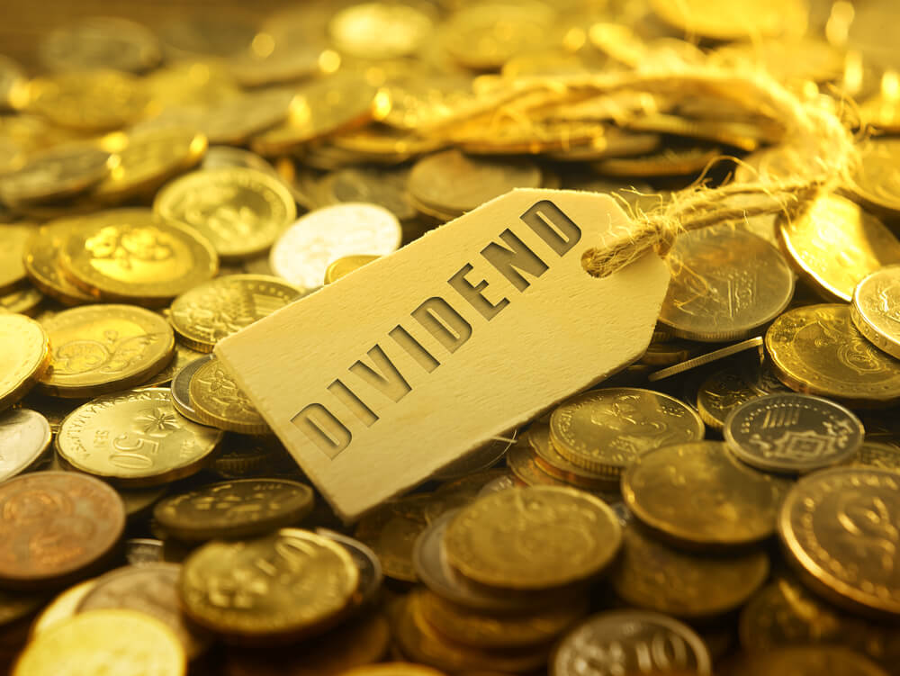 Dividend concept tag on top of piles of coins