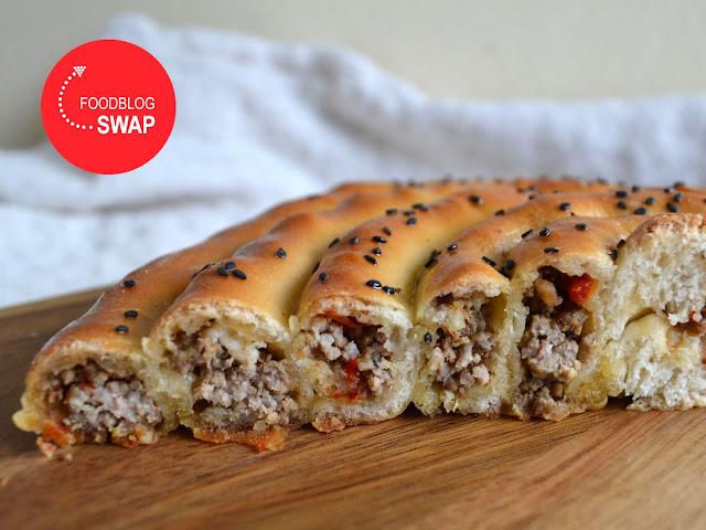 Door de helft gesneden broodmhancha (opgerold brood) met gehakt, paprika en geitenkaas